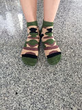 Selfie Feet Wearing Green Camouflage socks on Tile background Royalty Free Stock Photos