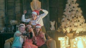 Selfie felice delle prese degli amici Celebrazione di natale Gli amici divertendosi, ridendo, fanno smorfie vicino all'albero di  archivi video