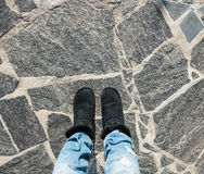 Selfie of foot and legs with black shoes and blue jeans Stock Photo