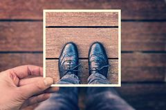 Selfie of foot and legs seen from above with hand holding an instant photo frame, vintage process Royalty Free Stock Image