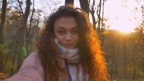 Selfie-foto de la muchacha caucásica rizado-cabelluda que mira risueñamente en cámara y que guiña en ella en parque otoñal solead foto de archivo