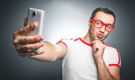 Selfie. Freak guy with pursed lips taking a selfie photo over dark gray background. Studio shot Stock Photos