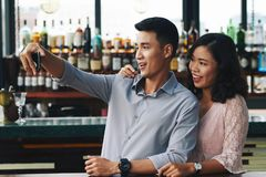 Selfie with friend. Cheerful young Asian men taking selfie with his female friend Stock Images
