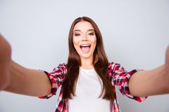 Selfie and funky mood! Attractive young amazed brunette lady is. Making a selfie on the camera, playful and happy. In casual wear, standing on pure light Royalty Free Stock Photo