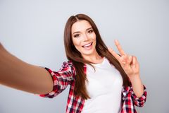 Selfie and funky mood! Peace! Cute young amazed brunette lady is. Making a selfie on the camera, playful and happy. In casual wear, standing on pure light Royalty Free Stock Photography