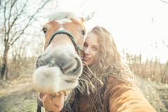 Selfie with funny face horse. Pretty young girl taking a funny selfie with a hilarious horse stock photo