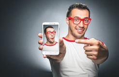 Selfie. Funny man showing on mobile phone - smartphone hie selfie photo. Jokes image at trendy time Royalty Free Stock Photo