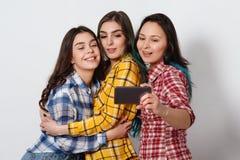Selfie - Gelukkige tienersvrouw die beelden zelf op witte achtergrond nemen royalty-vrije stock foto's