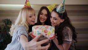 Selfie girlfriend bite cake birthday girl. Selfie three friends with a beautiful cake for the birthday girl