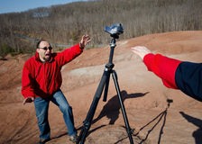 Selfie Gone Wrong. Videographer rushing to catch the tripod mounted falling camera. Another hand is trying to push or catch the camera. Accident, prank or help Stock Photography