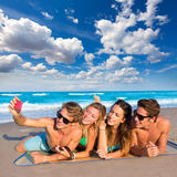 Selfie group of tourist friends in a tropical beach. Selfie photo of young friends group in a tropical beach lying on sand Stock Photos