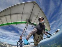 Selfie ha sparato del pilota di deltaplano che sale i updrafts termici fotografia stock