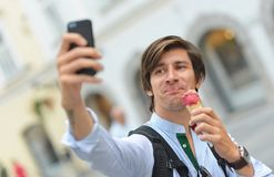 Selfie of handsome young man eating ice cream Stock Images