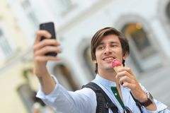 Selfie of handsome young man eating ice cream Royalty Free Stock Photos