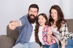 Selfie. Happy family at home. Modern smartphone. Little girl use smartphone with mother and father. bearded man and. Selfie. Happy family at home. Modern royalty free stock images