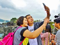 Selfie. Happy people make selfie at the geopark outdoor, Jusangjeolli Cliff, Bay of Jungmun area Seogwipo, Jeju Island, South Korea