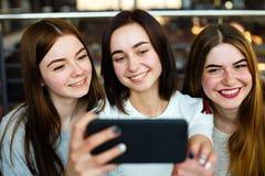 Selfie heureux de prise d'amies de jeunes femmes ensemble Photos stock