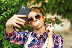 Selfie hipster girl with lollipop and chewing gum stock images