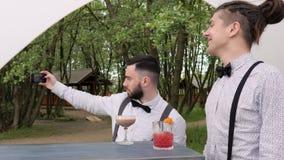 Selfie i arbetsplatsen, barkeeper gör fotoet i mobilen, alkohol bak stången, färgade kylde drinkar på stångräknare stock video