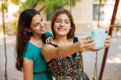 Selfie with an instant camera. Pretty teen friends taking a selfie with an instant camera while hanging out at a park Royalty Free Stock Image