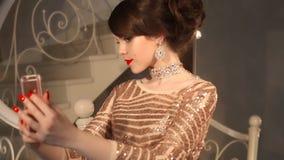 Selfie Jonge tiener die foto in gouden kleding en juwelen nemen Elegante dame in lovertjekleding het stellen door spiegel met stock footage
