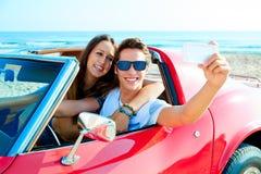 Selfie joven de los pares feliz en coche del res en la playa Fotografía de archivo