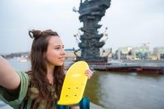 Selfie lindo del makihg de la muchacha del inconformista con el monopatín al aire libre en luz de la puesta del sol Mujer deporti Fotos de archivo libres de regalías