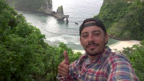 Selfie man Det manliga tagande den självfotoet och showen tummar upp det near härliga landskapet, den Atuh stranden och havet, Nu arkivfilmer