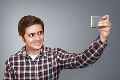 Selfie. Man doing selfie on grey background Royalty Free Stock Images