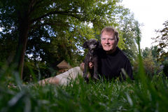 Selfie of Man holding Pet Dog. Selfie made by a mature man, smiling and holding his pet dog, a Poodle. The camera was placed on the ground in the yard, so grass Royalty Free Stock Photos