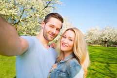 Selfie, man, woman, couple, friends. Young couple take a selfie with blooming trees in background stock images