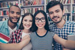 Selfie mania! Four international students with beaming smiles ar. E posing for selfie shot, asian attractive lady is taking, in school library building. Gathered Royalty Free Stock Image