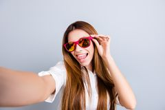 Selfie mania! Funky mood. Attractive young lady is making a selfie on the camera, flirty and playful. In pink trendy sunglasses, w. Ith tongue out, on pure light stock images