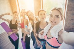 Selfie mania in gym! Five girlfriends in fashionable sport outfits are posing for a selfie photo, that blond is taking. They are. All smiling, joyful after the royalty free stock photo