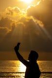 Selfie-Mann-Smartphone-Seesonnenaufgang-Schattenbild Lizenzfreies Stockfoto