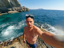 Selfie mette in mostra l'operatore subacqueo degli uomini nella maschera che sta sulla riva del mare in costume da bagno Fotografia Stock