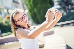 Selfie Moça bonito bonita com cintas e vidros que ri para um selfie foto de stock