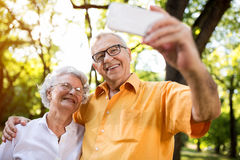 Selfie with mobile. Senior couple taking selfie with mobile in nature Stock Photo