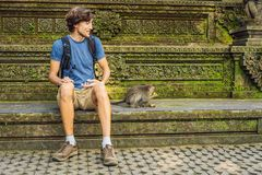 Selfie with monkeys. Young man uses a selfie stick to take a photo or video blog with cute funny monkey. Travel selfie with. Wildlife in Bali stock image