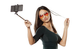 Selfie with monopod. Pretty brunette with sunglasses making selfie with monopod Royalty Free Stock Images
