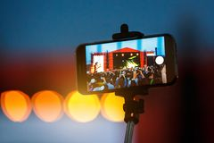 Selfie monopod stick and cellphone. Concert background Stock Photo