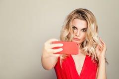 Selfie Mujer rubia hermosa con maquillaje y tomar del pelo rizado Foto de archivo