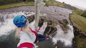 Selfie na câmera da ação da mulher bonita nova que voa para baixo no tirante com mola com a maneira da corda sobre o rio vídeos de arquivo