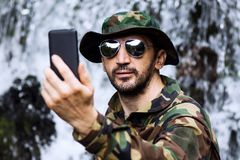 Selfie in nature. Man in military uniform is taking selfie and using phone in nature, adventure in nature stock image