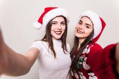 Selfie Nehmen mit zwei Frauen von den Händen in Sankt-Hut Lizenzfreies Stockbild