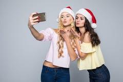 Selfie Nehmen mit zwei Frauen von den Händen in Sankt-Hut lokalisiert auf weißem Hintergrund Drei Weihnachtskugeln getrennt auf W Stockfotos