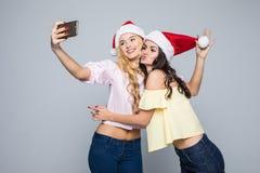 Selfie Nehmen mit zwei Frauen von den Händen in Sankt-Hut lokalisiert auf weißem Hintergrund Drei Weihnachtskugeln getrennt auf W Lizenzfreie Stockbilder