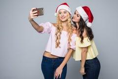Selfie Nehmen mit zwei Frauen von den Händen in Sankt-Hut lokalisiert auf weißem Hintergrund Drei Weihnachtskugeln getrennt auf W Lizenzfreies Stockfoto