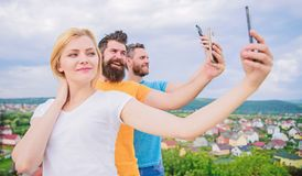 Selfie with no filter. Best friends taking selfie with camera phone. Pretty woman and men holding smartphones in hands royalty free stock image