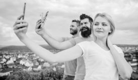 Selfie with no filter. Best friends taking selfie with camera phone. Pretty woman and men holding smartphones in hands stock photo